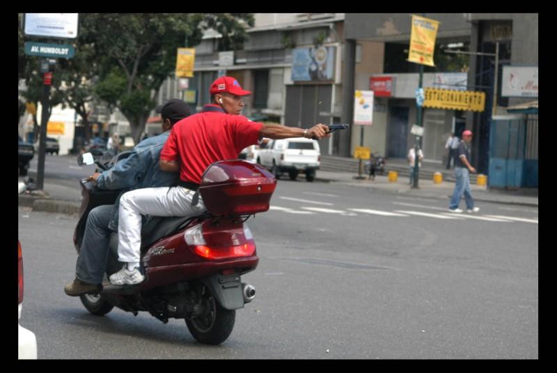 Un efectivo policial dispara su arma de reglamento contra un grupo de manifestantes adversos al presidente venezolano Hugo Chávez.  El hecho ocurrió en la avenida Casanova, de Caracas, capital venezolana.